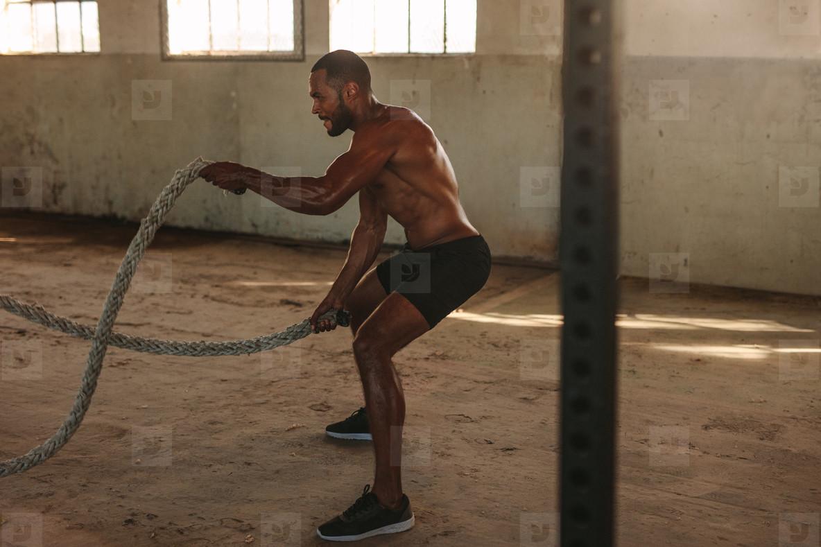 Muscular man doing battle rope workout