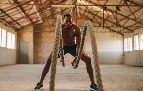 Muscular man working out with battle ropes