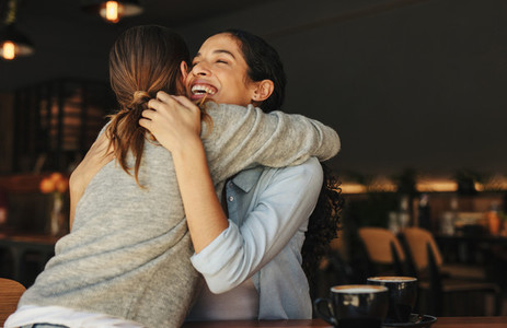 Female friends greeting each other with a hug in a cafe