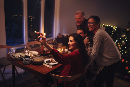 Family taking selfies at Christmas dinner table
