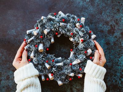 Girls hands in a winter white sweater hold a Christmas holiday wreath on a blue table