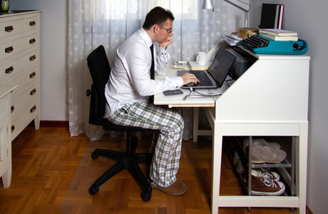 Man teleworking wearing shirt  tie and pajama pants