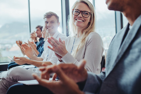 Group of businesspeople clapping hands at seminar