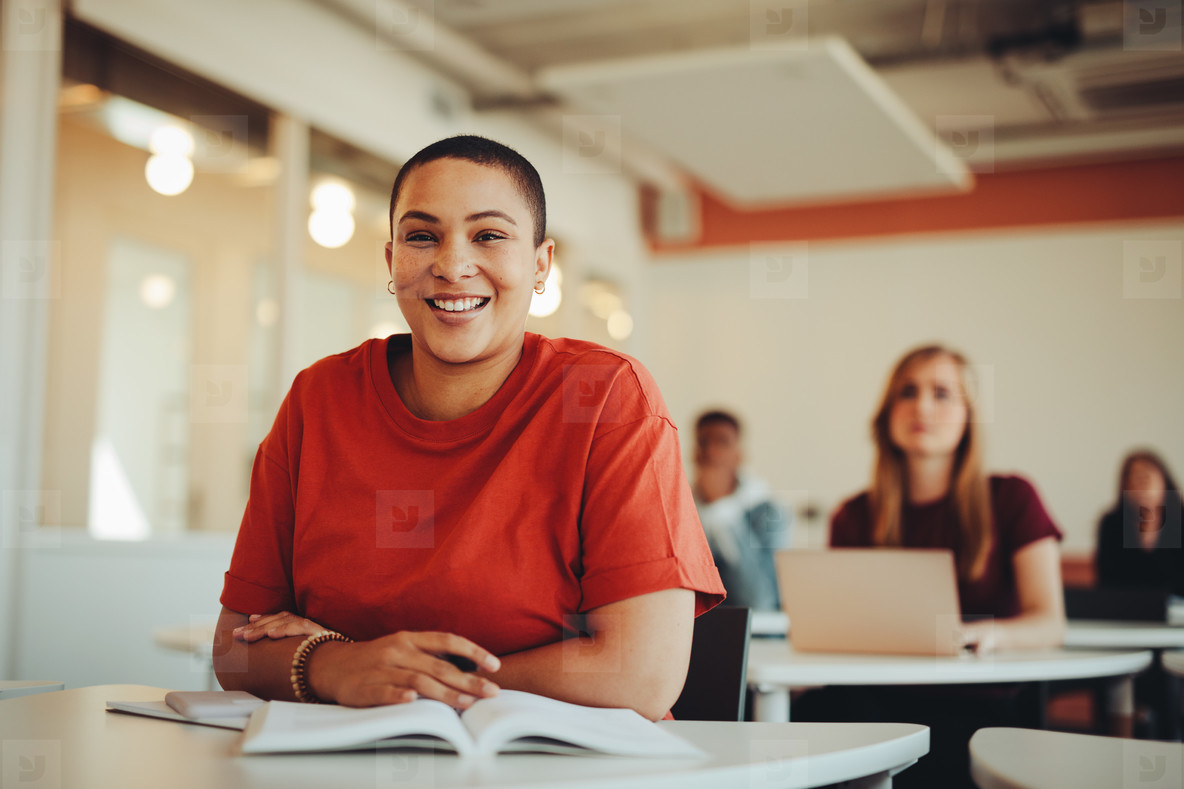 Portrait of a smiling girl sitting in university classroom