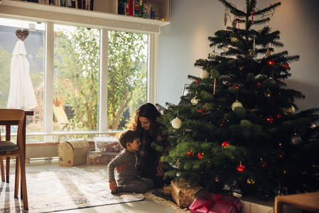 Mother and son sitting by Christmas tree