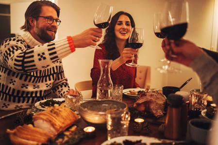 Happy family toasting wine and enjoying Christmas dinner