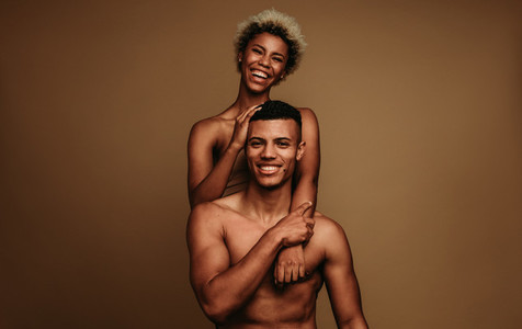 Happy african american couple together on brown background