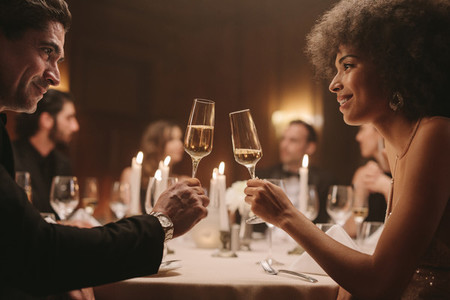 Couple at gala dinner party celebrating with drinks