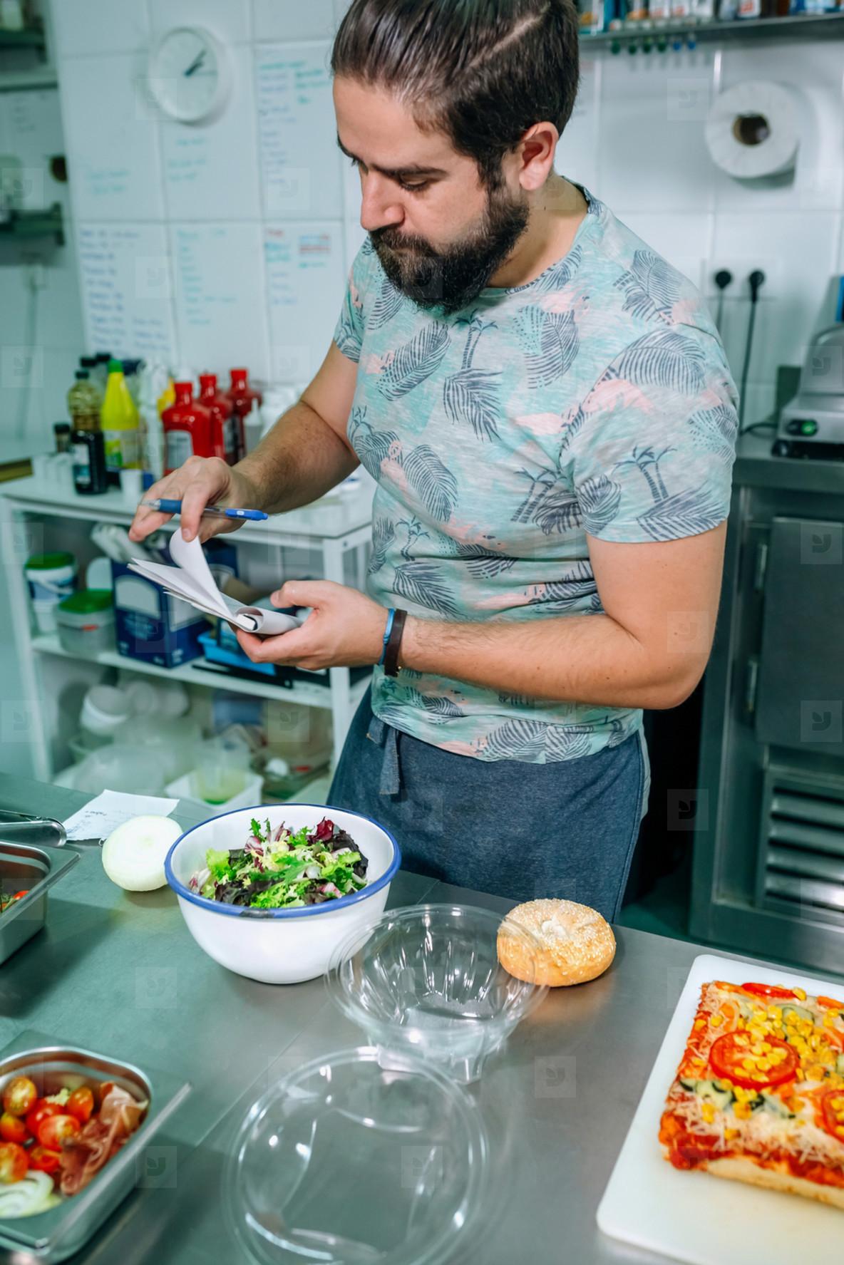 Young cook preparing takeaway orders