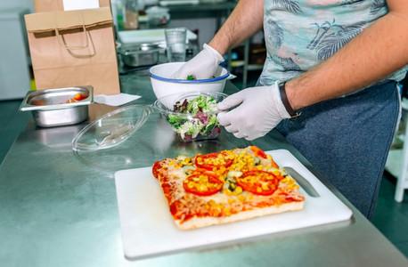 Unrecognizable cook preparing takeaway orders