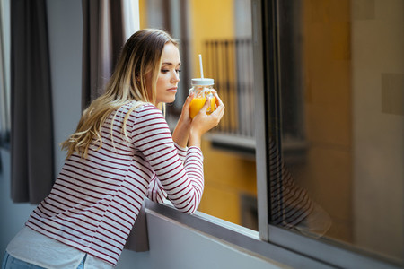 Young woman drinking a glass of natural orange juice leaning out the window of her home