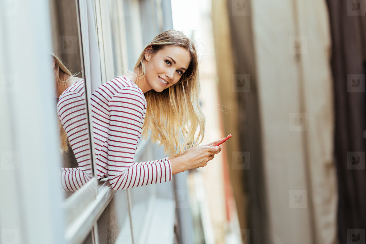 Young woman leaning out of her house window using a smartphone