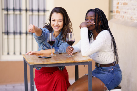 Two women drinking red wine sitting at a table outside a bar