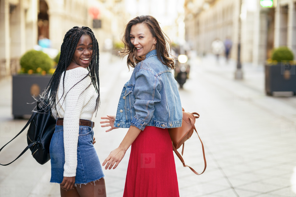 Two female friends having fun together on the street  Multiethnic friends