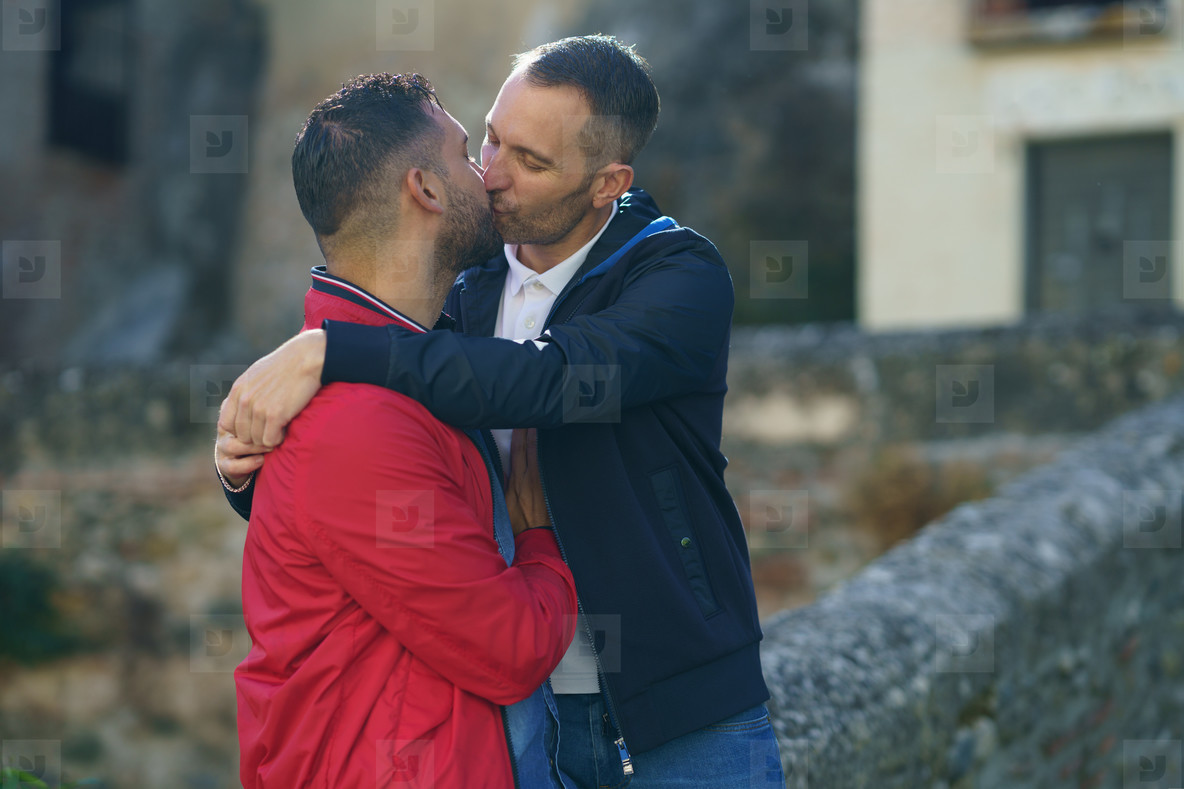 Gay couple kissing a beautiful place near the river