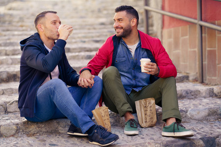 Gay couple having a take away meal on the street