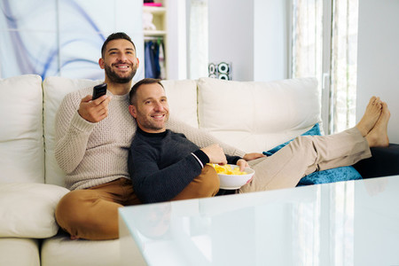 Gay couple sitting on the couch at home watching something on TV and having a snack