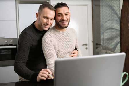 Romantic Gay couple working together at home with their laptops