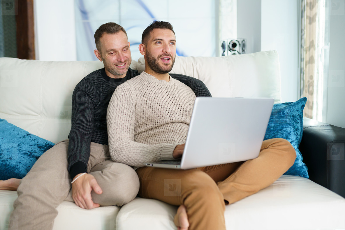 Gay couple consulting their travel plans together with a laptop