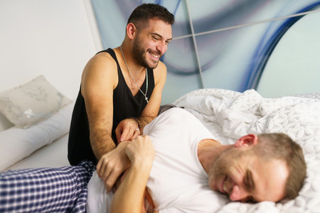 Gay couple tickling each other in bed