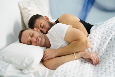 Gay couple sleeping together hugging in bed