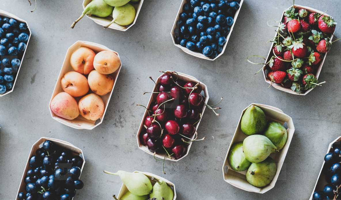 Fresh summer fruits and berries over grey concrete background