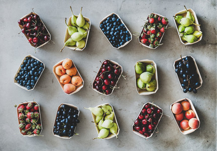 Flat lay of various fruits and berries over grey concrete background