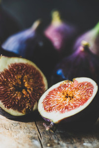 Fresh ripe seasonal purple figs over wooden board  close up