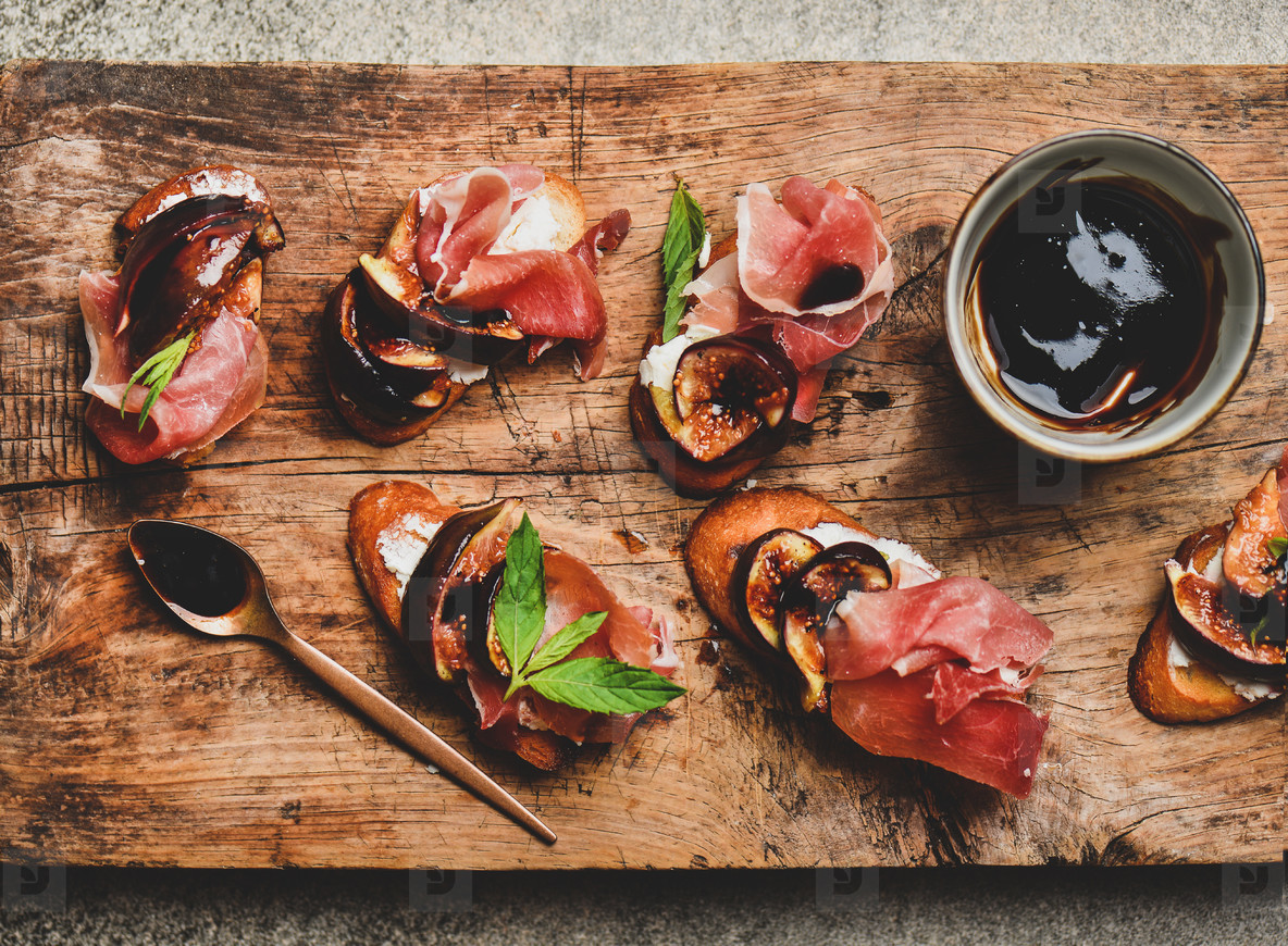 Crostini with prosciutto  cheese and figs on wooden board