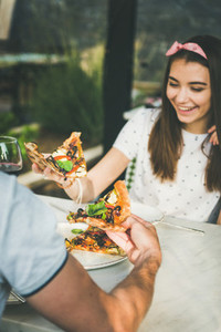 Young caucasian couple eating pizza and drinking wine in restaurant