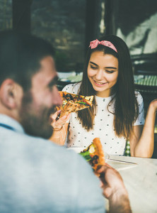 Young happy caucasian couple eating pizza in cafe