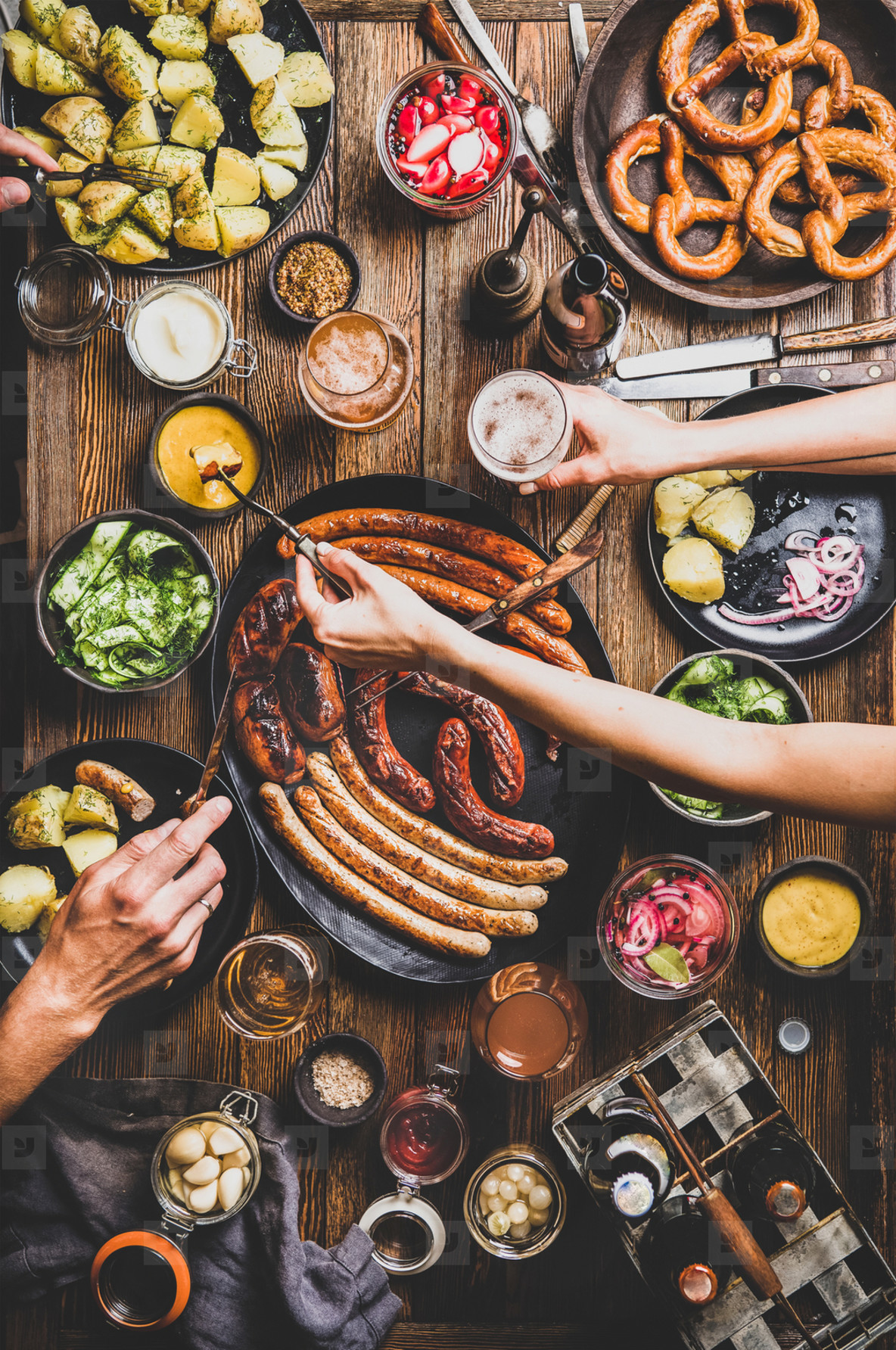 Octoberfest dinner table with beers  sausages  peoples hands with snacks