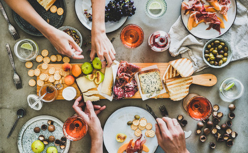 Summer picnic with rose wine and snacks and peoples hands
