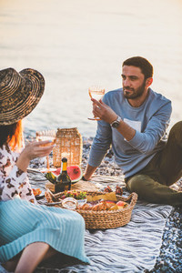 Young couple having picnic with sparkling wine and fruit