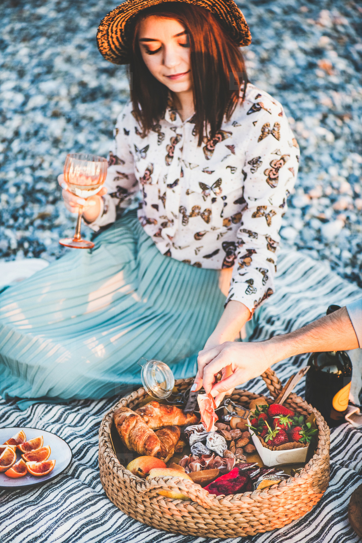 Couple having picnic at seaside with sparklng wine and appetizers