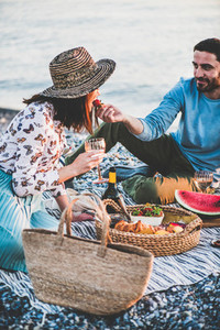 Young man feeding woman with strawberry during summer picnic
