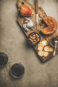 Glasses of red wine and various snacks on wooden board
