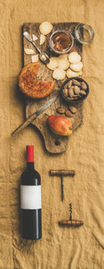 Wine bottle  vintage corkscrews and appetizers board  vertical composition
