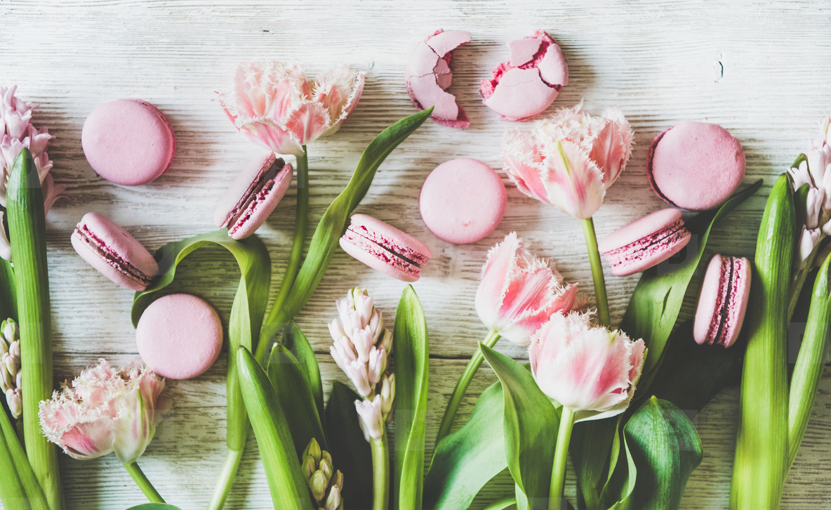 Sweet pink macaron cookies and spring fresh flowers  top view