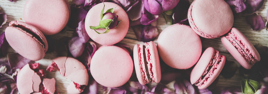 Sweet macaron cookies and rose buds and petals  wide composition