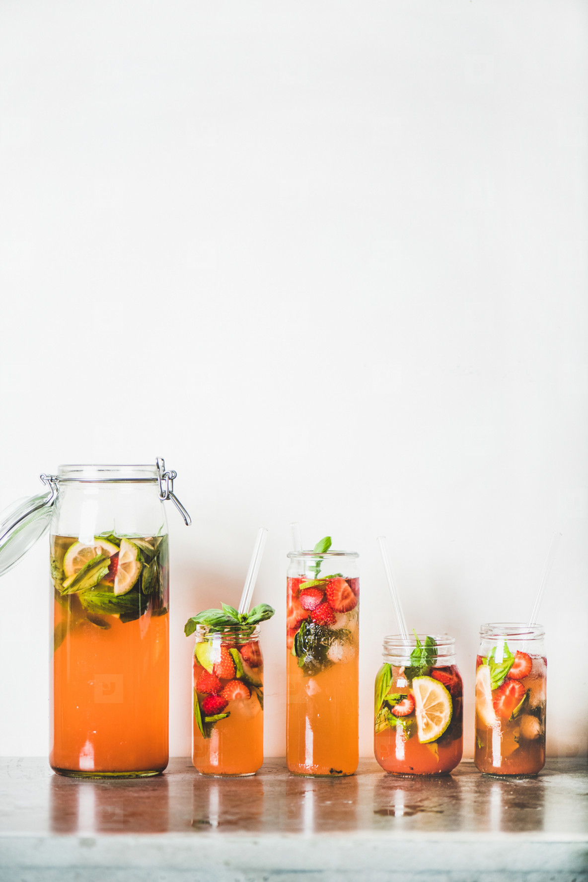 Homemade strawberry and basil lemonade or ice tea in glasses