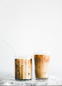 Homemade iced latte coffee in glasses with straws on table