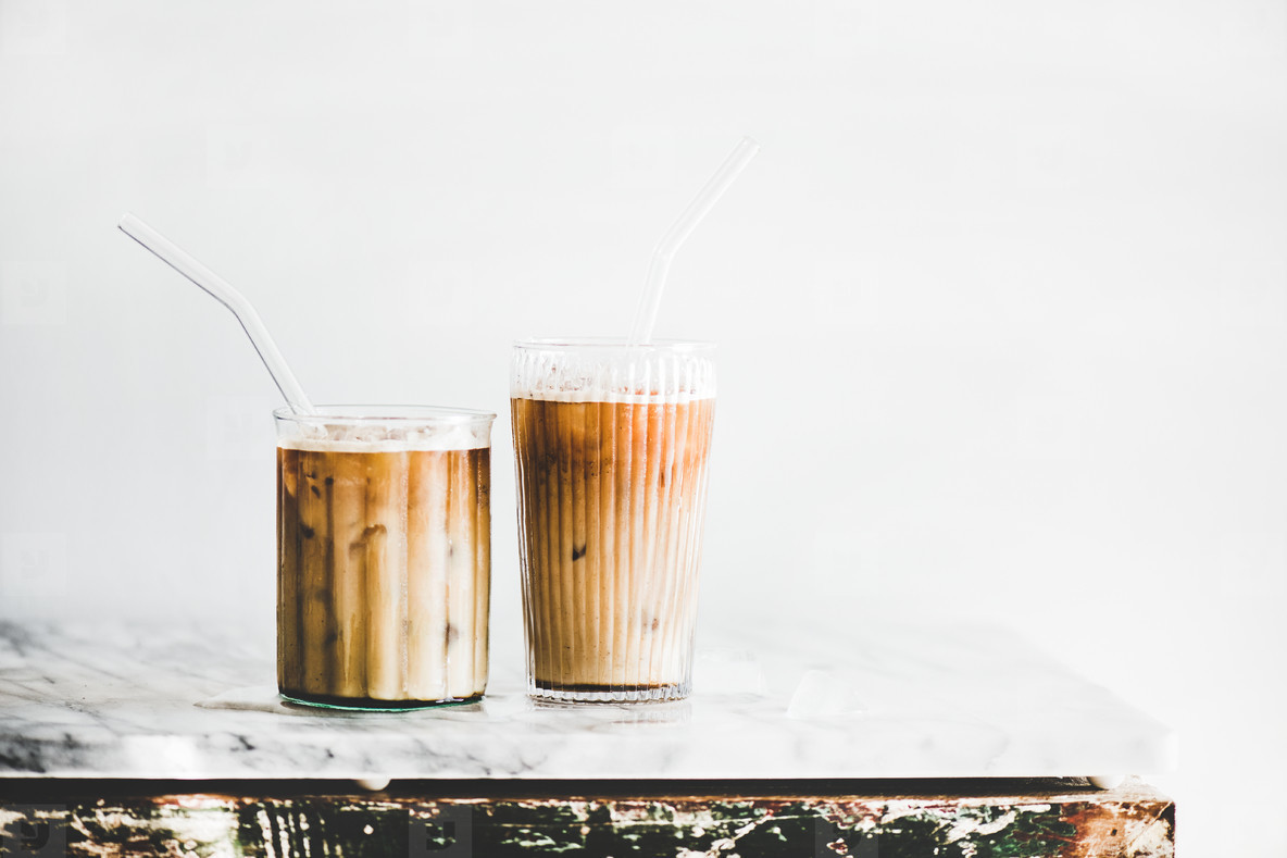 Iced latte coffee in glasses with straws  whate wall background