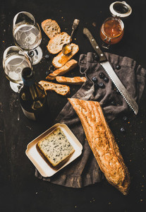 White wine baguette cheese and jam over dark background