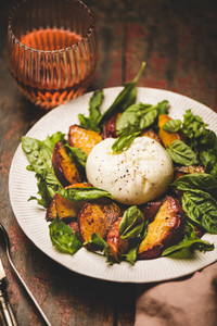 Seasonal salad with burrata cheese and glass of rose wine