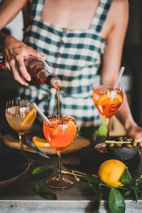 Young woman pouring aperol liquor to alcohol cocktail spritz
