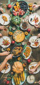 Friends feasting at Thanksgiving Day table with turkey narrow composition