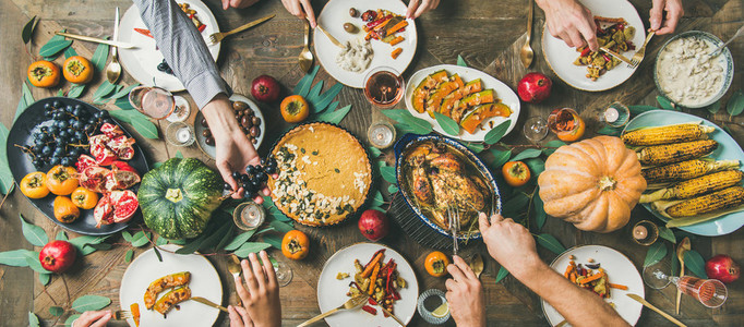 Friends feasting at Thanksgiving Day table with turkey  wide composition