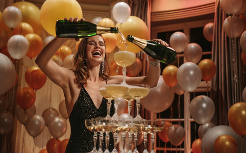 Excited woman filling up champagne pyramid at party