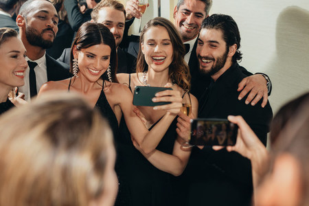 Beautiful woman taking selfies with his friends at a party